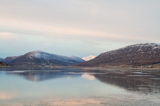 雪に覆われた岩に囲まれ、アイスランドの水面に映る海