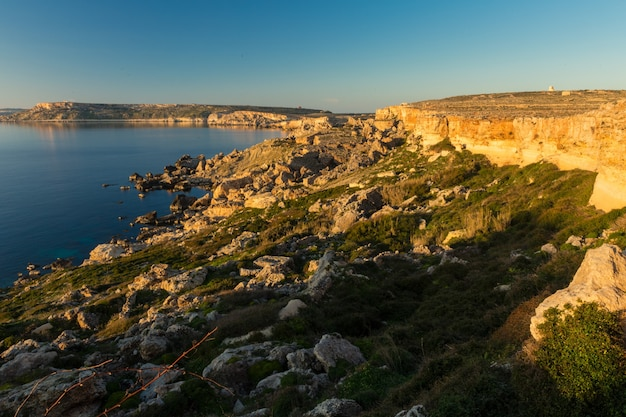 Sea surrounded by rocks under the sunlight and a blue sky in north-western coast , malta