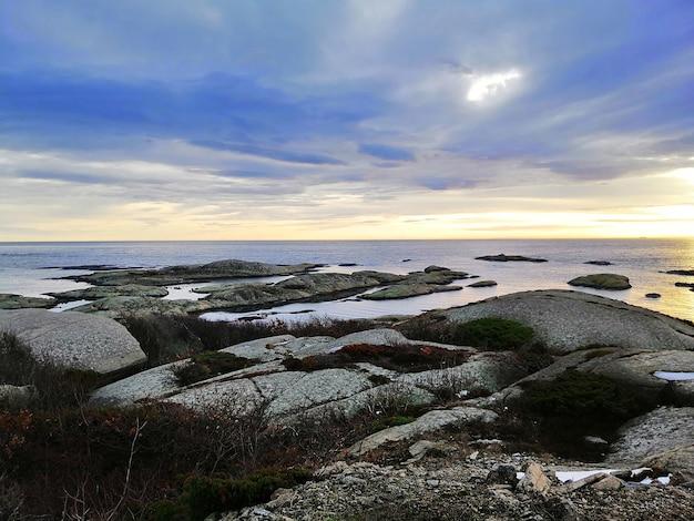 ノルウェーのラッケで日没時に曇り空の下で岩に囲まれた海