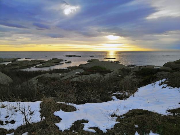 ノルウェーのラッケの日没時に曇り空の下で岩に囲まれた海