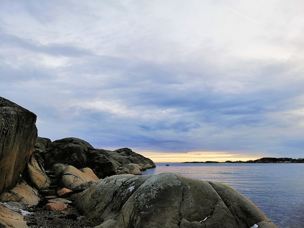 ノルウェーのスタバーンで日没時に曇り空の下で岩に囲まれた海