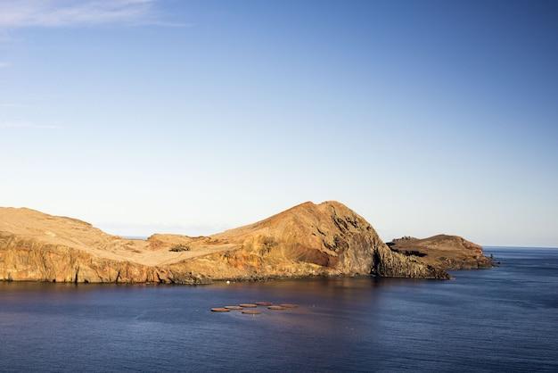 ポルトガルの日中の日光と青い空の下で岩に囲まれた海