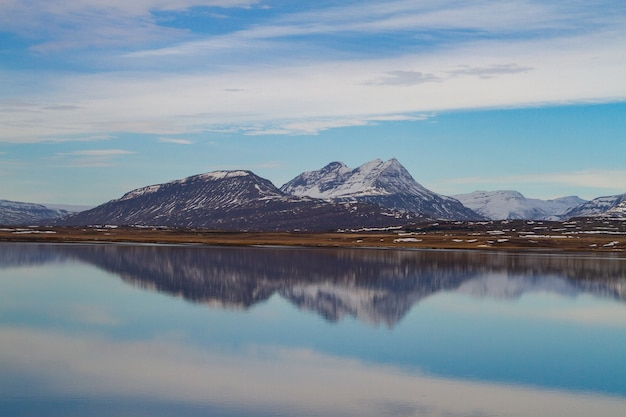 Sea surrounded by rocky mountains covered in the snow and reflecting on the water in iceland