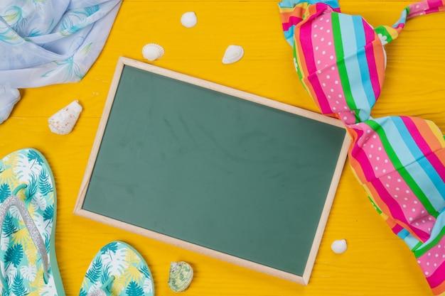 海の観光、黄色の木の床にさまざまなオブジェクトを配置した緑のライティングボード。