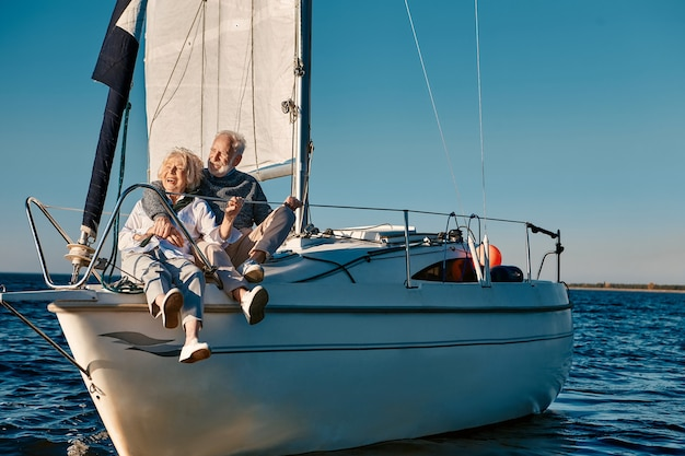 帆船でリラックスしながら抱き締めて楽しんで海の旅幸せな美しい先輩家族のカップル