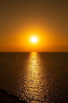 Морской вертикальный пейзаж. дорожка в море от солнца на закате. летние каникулы и путешествия.