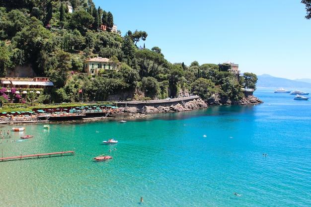 Sea view of beautiful italian city on liguria coast, beach, people swimming