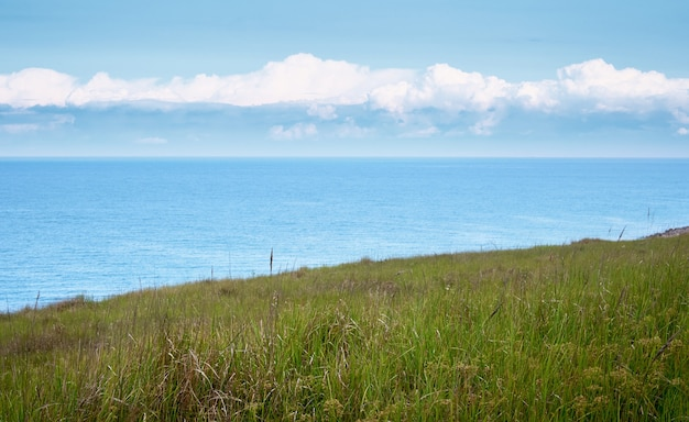 Sea view from a hill overgrown with green grass with clouds on the horizon