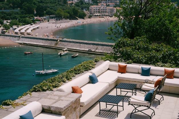 바다 전망 레스토랑 아늑한 소파와 베개와 연철 의자가 물 근처에 있습니다.
