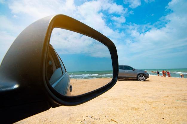 車のサイドミラーからの海の眺め。海岸の車。