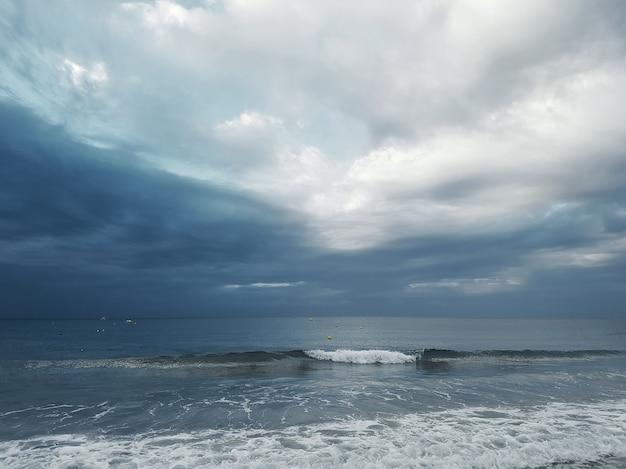 Вид на море с бегущими волнами на фоне темного неба с кучевыми облаками.
