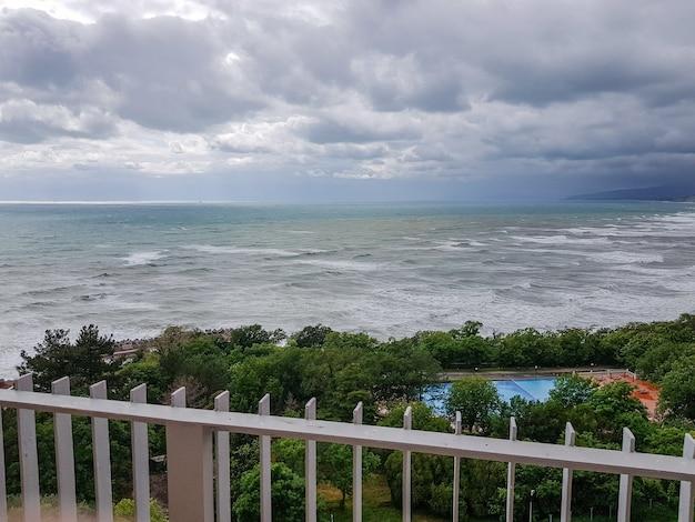 ホテルのテラスからの波と空の海の景色、朝、曇り、夜明け。