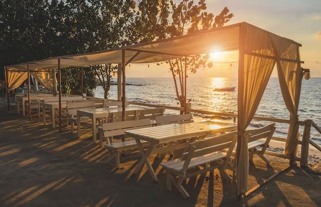 白いデザインのテーブルと日の出照明付きのファブリックで海の景色。