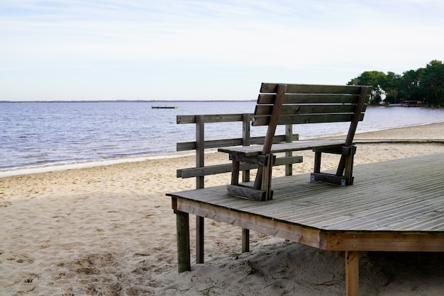 Sea view in wooden terrace with wood bench in sand lake beach