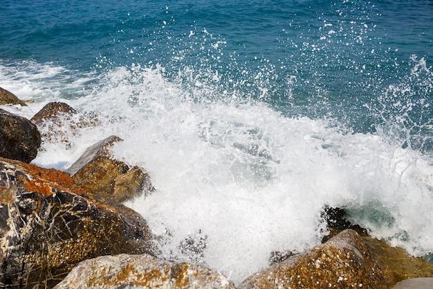Морская вода бьется о скалы и образует волны пеной.