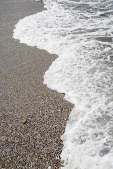 해변에 거품이 있는 파도의 바닷물