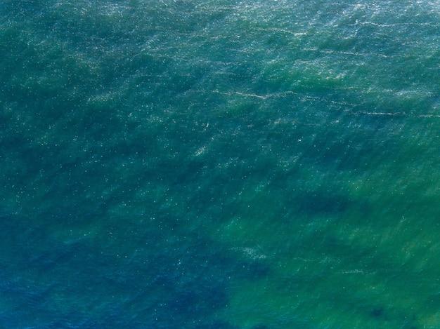 海の水面、テキストの場所と海の青い背景。抽象的なアクアまたは液体のテクスチャ、パターン。ドローンからの空撮。