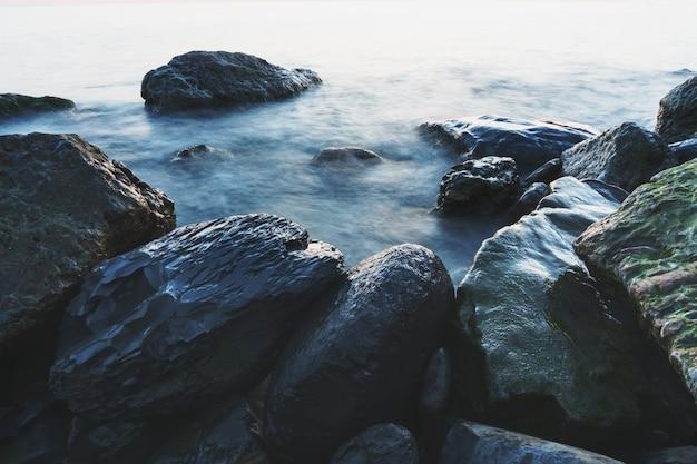 Морская вода омывает скалы на берегу. снимок моря с длинной выдержкой