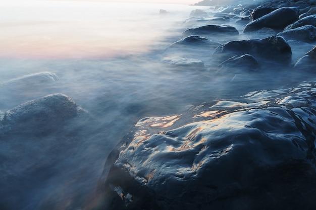 Морская вода омывает скалы на берегу.