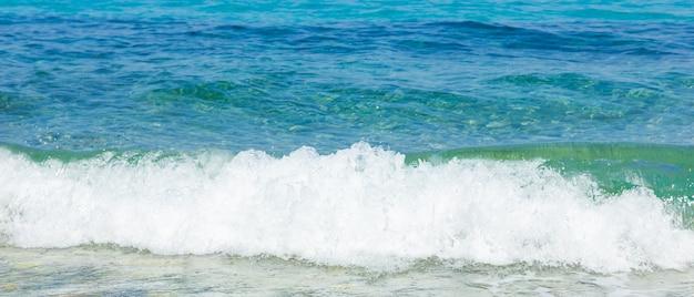 Морская волна и галька. концепция летних каникул. морская волна с пеной падает на прибрежную гальку. концепция путешествия