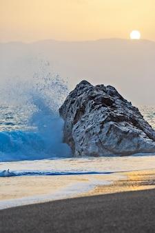 日没時に岩に勢いよく打ち寄せる海の波