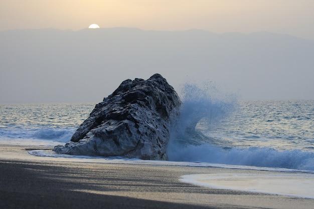 일몰에 대 한 바위에 바다 파도 뛰는
