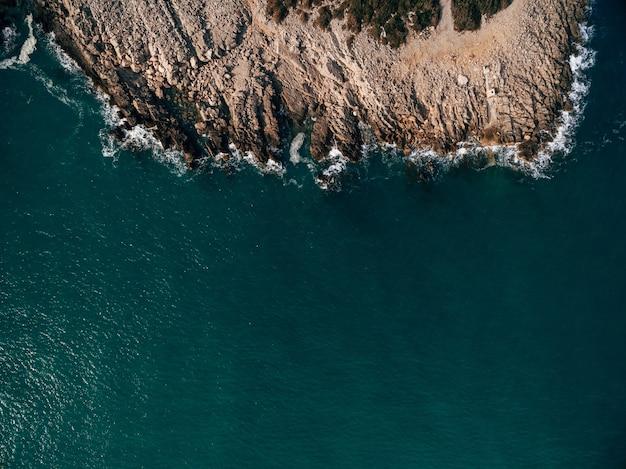 アドリア海沿岸の岩に打ち寄せる海の波がスプレーと泡のドゥブロヴニククロアチアを生み出している
