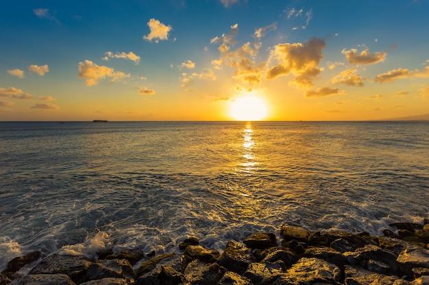 ハワイの日没で海の波が岩を打つ