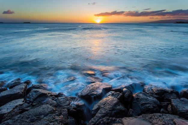 ハワイの日没で海の波が岩に当たった