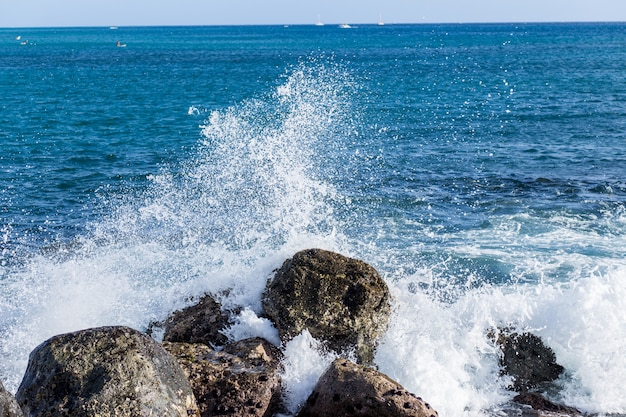 Морская волна ударилась о скалу