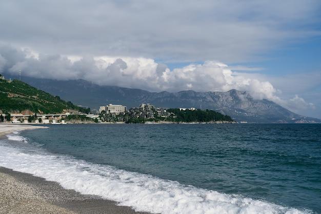 바다 물결은 산과 건물을 배경으로 자갈 해변에서 흐릅니다.