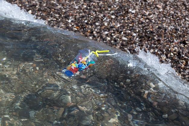 바다 파도가 일회용 플라스틱 쓰레기를 해변에 던졌습니다 바다의 오염 오래 썩어가는 가정 쓰레기