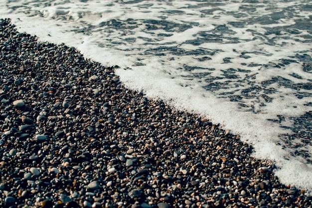 小石のビーチで泡と海の波