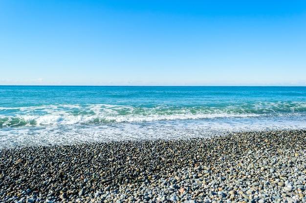 石の多いビーチで砕ける海の波、日没時に水しぶきや水しぶきを形成