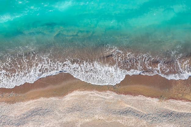 黄色い砂浜で砕ける海の波、真上からの上面図