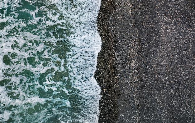 Морские волны разбиваются о дикий пляж с черным песком и галькой, воздушный естественный фон