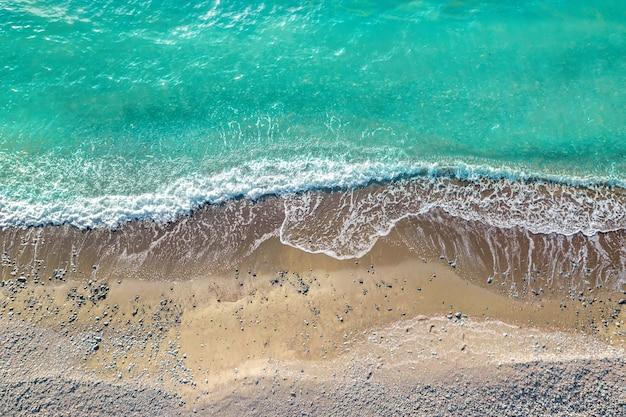 砂と小石のある野生のビーチで砕ける海の波、真上からのドローンの視点