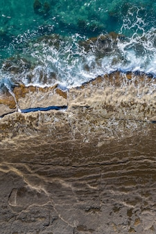 Sea waves breaking on rocky shore, aerial vertical shot directly above