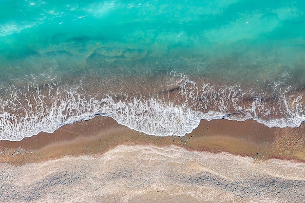 Sea waves breaking on a yellow sand shore, top view directly above
