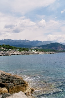 Sea waves hit the rocky shore against the backdrop of mountains greenery and buildings