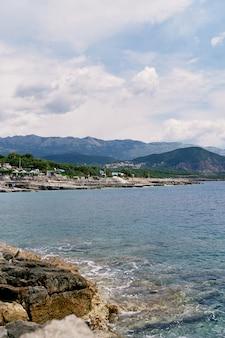 바다 파도는 산의 녹지와 건물을 배경으로 바위 해안을 친다