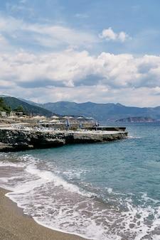 일광욕용 라운저와 파라솔이 있는 바위 해안에 파도가 치다
