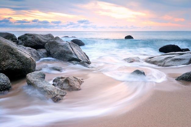 Sea waves lash line impact rock onthe beach