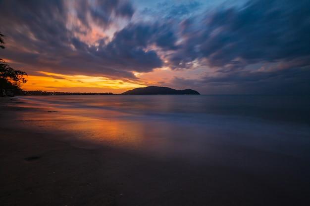 海の波がビーチでラインモーションをラッシュし、日の出で雲