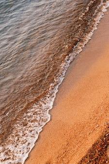 Морские волны бегают по оранжевому песку на пляже