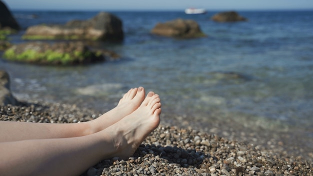 Морские волны омывают загорелые женские ступни. красивая молодая женщина расслабляющий на побережье во время летних каникул. ноги девушки, лежащей на пляже в солнечный день. крупным планом медленное движение