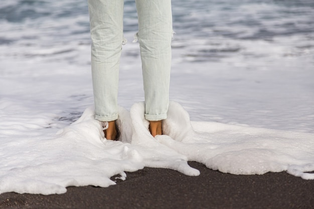 ライトブルージーンズの女性の足を洗う白い優しい泡と海の波。ビーチの砂の上に立っている女性の足。