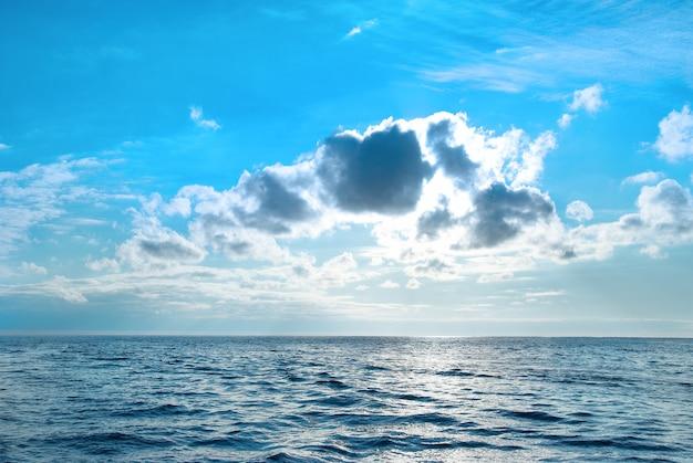 Море с голубой водой, небом и облаками. закат над морским пейзажем
