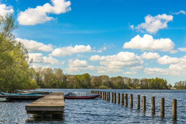 ドック近くのボートと青い空の下で遠くに緑の木々と海