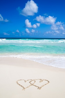 Sea with hearts written in the sand